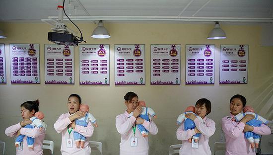 """2018年12月5日,北京,家政服务培训项目""""阿姨大学""""的学员上儿童保育课。来源:视觉中国"""