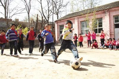 一所乡村学校的孩子们正在操场上踢足球。光明图片/视觉中国