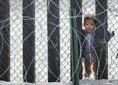 一名儿童透过边境墙从墨西哥一侧眺望美国。