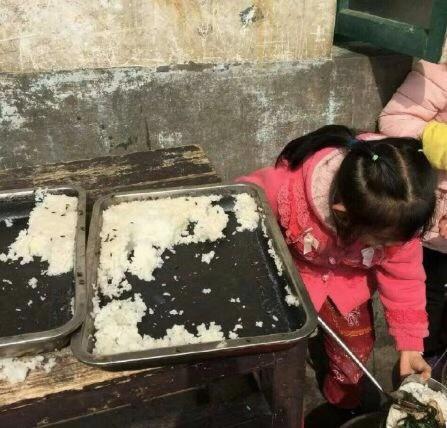 多张网传现场照片显示,蒸熟的大米上爬着不少苍蝇,一位红衣小女孩正在旁边打饭。