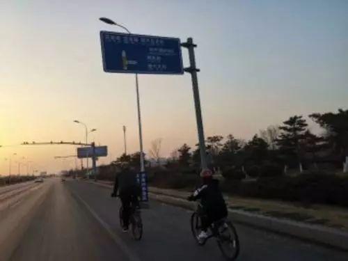 为了陪同李明钊安全骑行,其堂哥骑自行车陪同。