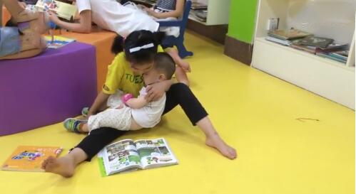 8岁女童抱着弟弟坐在地上看书