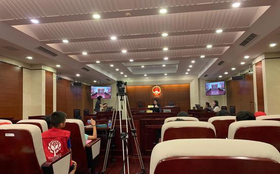 庭审中,原告站起来展示证据。新京报记者刘洋摄