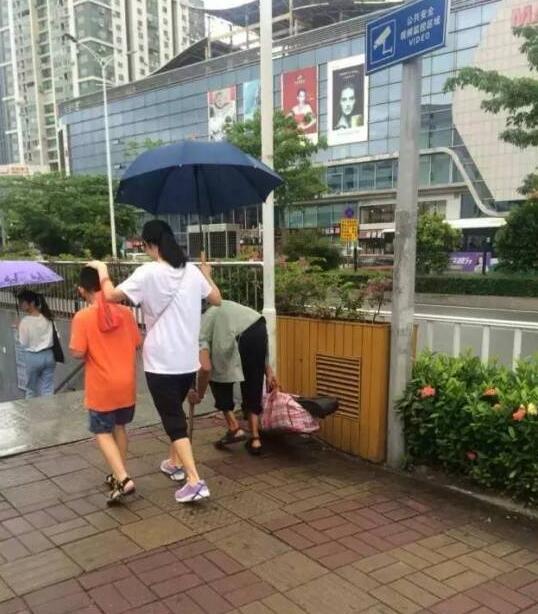 妈妈为流浪老人打伞,用手为儿子挡雨