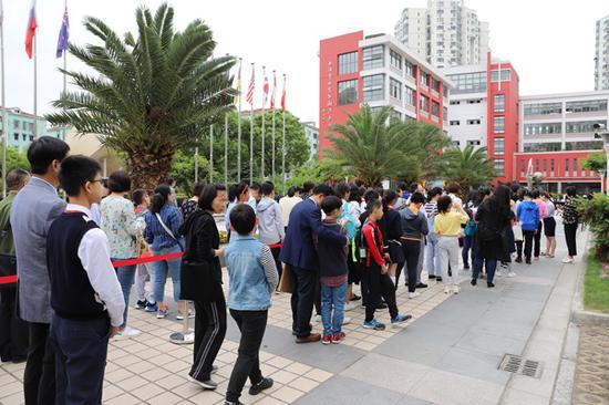 在世界外國語中學,學生、家長正有序候場。