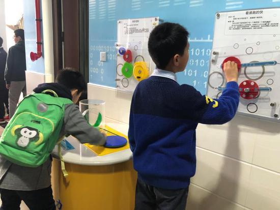 学生在民办进才外国语中学金融体验区和物理长廊体验。