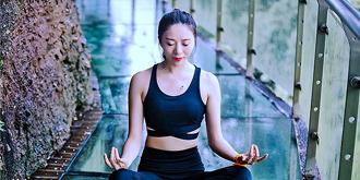 美女玻璃桥上练瑜伽