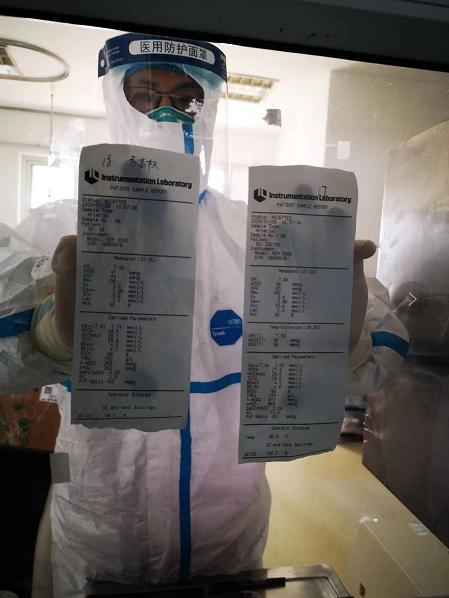 援鄂医疗队中大医院医生潘纯隔着玻璃把病人检查单给窗外医生看
