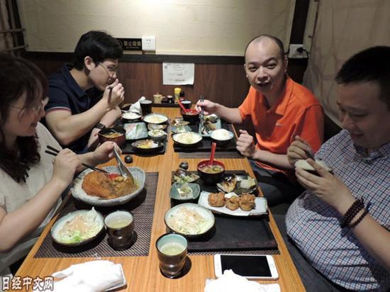 广州市的杨先生和同事一起吃日料。(《日本经济新闻》网站)