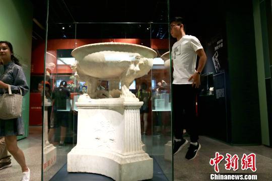 图为一名观众高高跃起参观文物。 张远 摄