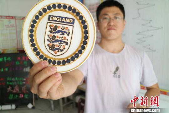 足球爱好者吕一民展示英格兰国家队队徽。