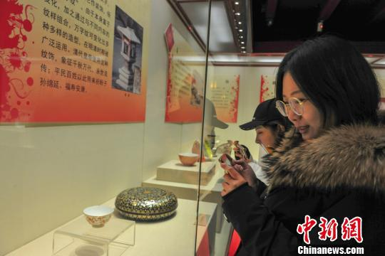 观众在现场观看带有吉语纹饰的清宫文物。 于海洋 摄