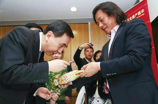 ▲2011年,时任广东省省长朱小丹在悉尼中国文化中心欣赏王芝文的陶瓷微书作品