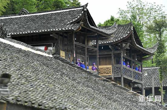 居民登上修缮后的彭家寨古吊脚楼。 新华社发(宋文 摄)