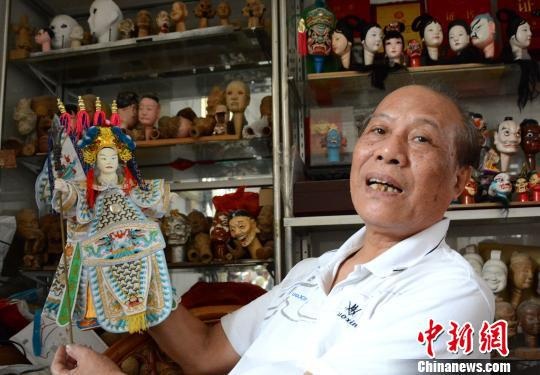 杨亚州展示木偶雕刻的伴手礼。 张金川 摄