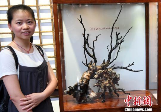 一名年轻女观众与参展海柳雕艺术精品合影 记者刘可耕 摄