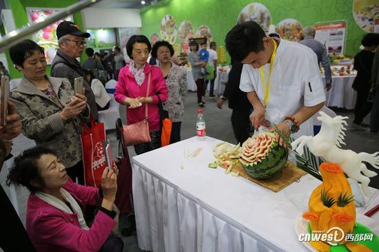 小田在西瓜上雕花,娴熟的手法,精美的花形很吸引人。
