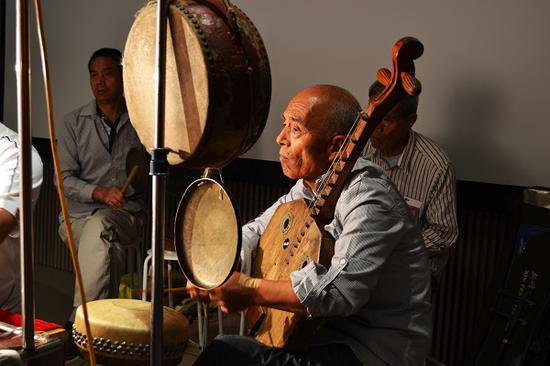开幕当日,来自陕西的皮影老艺人们正在为观众表演。
