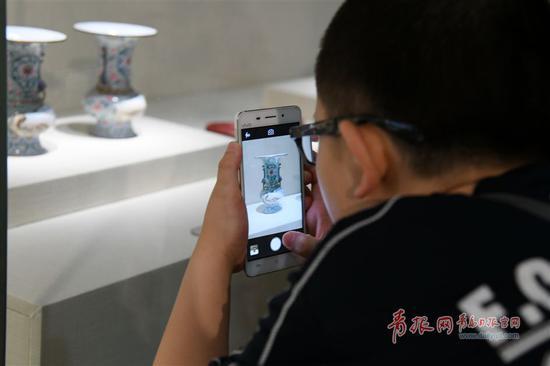 参观者用手机记录下自己喜欢的展品。