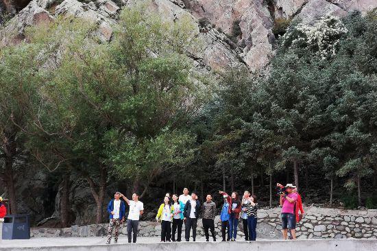 记者们在欣赏岩石间跳跃的岩羊。