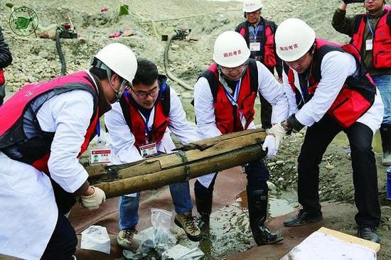 图说:考古人员将木鞘搬离发现地点。
