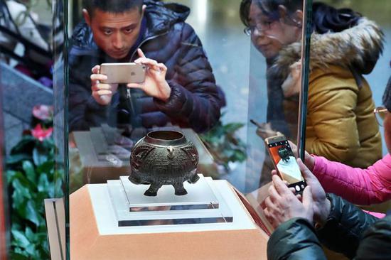 青铜猪形卣在上海博物馆一楼大厅展出,吸引许多参观者驻足。