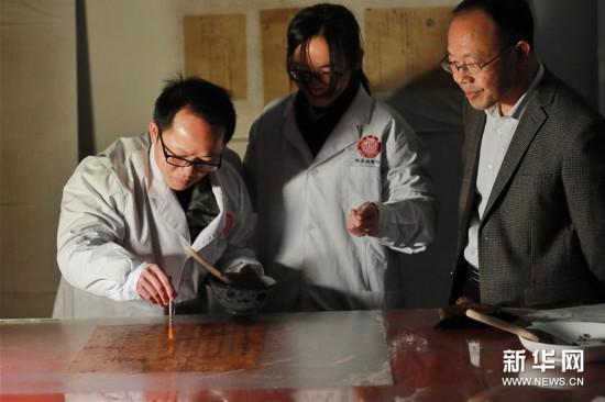 3月18日,王宗勋(右)在锦屏文书特藏馆内指导工作人员对锦屏文书进行裱糊。