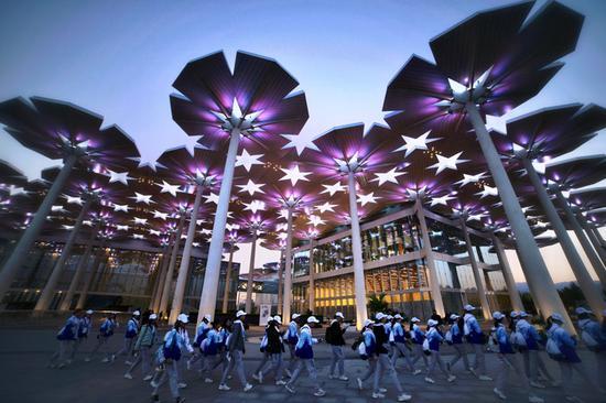 晚上7时,志愿者队伍从国际馆前经过。
