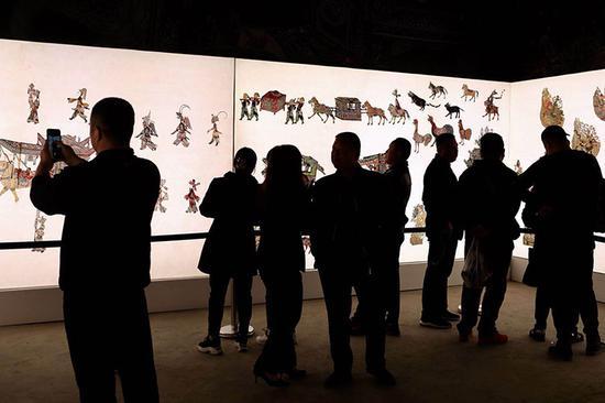 观众在欣赏皮影展。