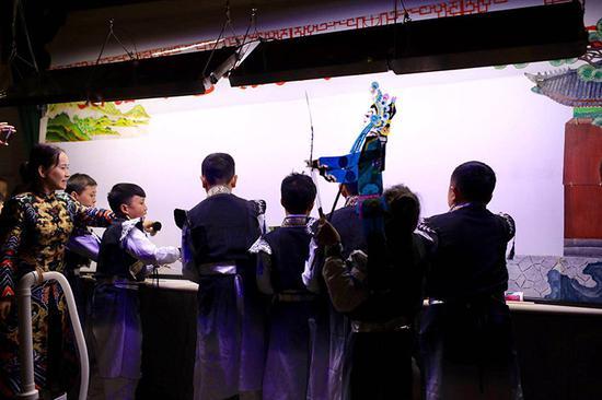 北京龙在天皮影团的小演员在表演皮影戏《白蛇传》。