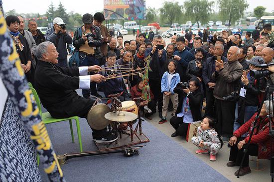 """75岁的世界级非遗山东泰山皮影戏传承人范正安在表演皮影独门绝技""""十不闲""""。"""