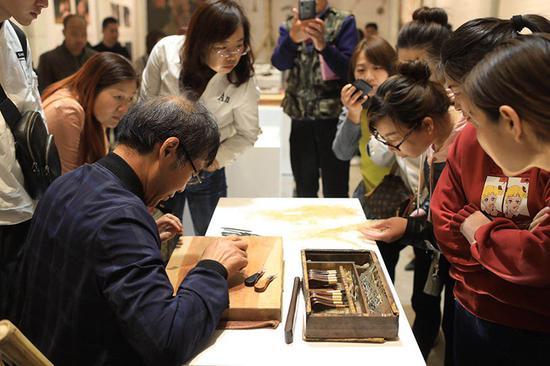 皮影雕刻传承人汪天喜在现场制作皮影。
