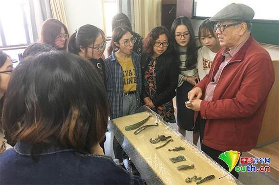 黄宏向学生们展示自己收藏的文物。资料图
