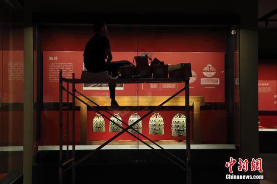 图为7月7日山西青铜博物馆工作人员正在进行灯光布置。中新社记者 张云 摄
