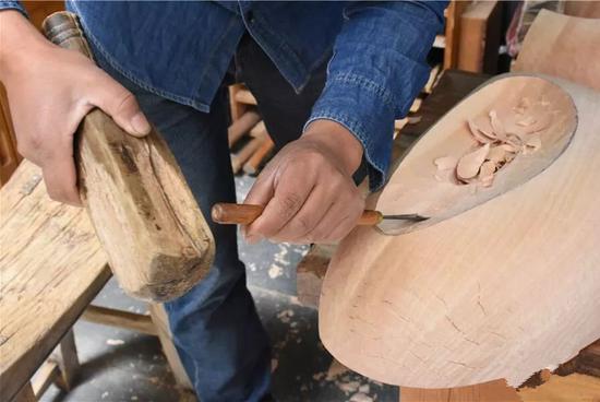 木雕打初坯阶段,用锤跟刀在木头上敲打,这是一个费体力的活计。