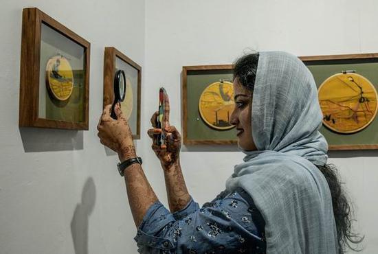 一位观众正在用放大镜观看并拍摄Bapi Das的作品