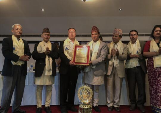 """尼泊尔法律、司法、议会、文化事务部部长塔芒(左四)给来自中国的唐卡收藏家乔国金先生(左三)颁发""""尼泊尔艺术文化使者""""证书"""