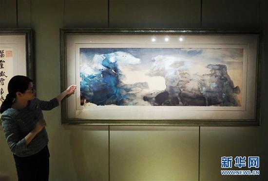 3月初,香港苏富比2018年中国书画春拍举行传媒预展。工作人员介绍张大千作品《春山瑞雪、行书七绝》。