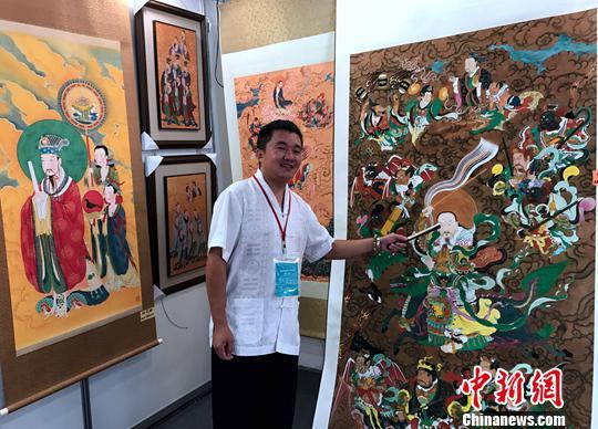 图为上海绘真堂总经理王琛介绍他带来的传统重彩工笔道教神像画。中新社记者 邢利宇 摄