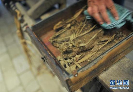 6月12日,罗小龙在展示打草鞋的过程。新华社记者 李任滋 摄