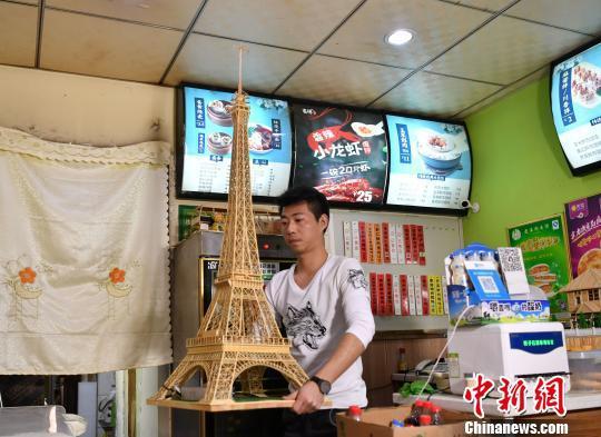 徐瑞斌展示自己的作品——埃菲尔铁塔模型。 翟羽佳 摄