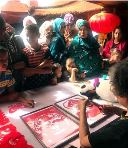 第14届摩洛哥坦坦非遗艺术节中国展台前充满好奇的民众