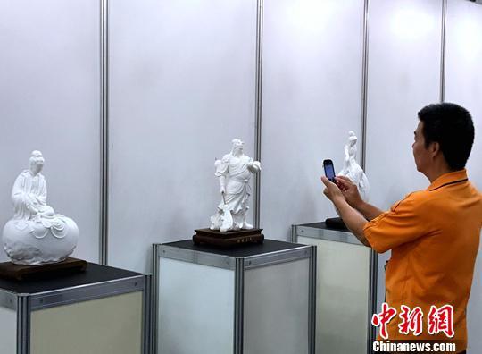 图为台湾民众参观福建陶瓷艺术大师李锦峰带来的白瓷雕塑作品。中新社记者 邢利宇 摄