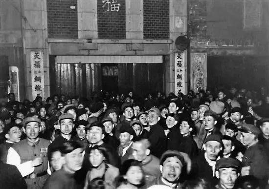 梅兰芳演出时,买不到或买不起票的市民在天福门口听演出广播