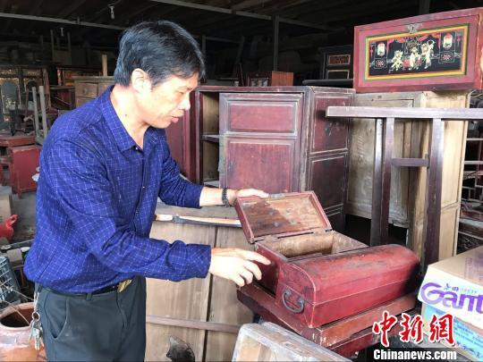 陈修俊展示他收藏的老物件。 郑松波 摄