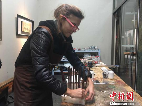 在工作台前,多米尼克·亨伯特正在用木坯筷子学习漆艺装饰。 叶秋云 摄