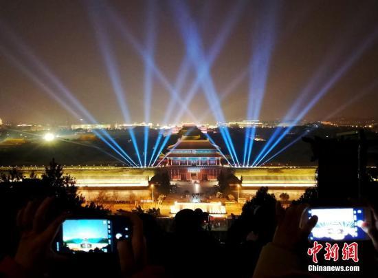 2月18日,元宵节将至,北京市民在景山公园拍摄故宫夜景。中新社记者 杜洋 摄