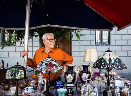 ↑8月4日,在意大利阿雷佐,一位商户在古董集市售卖商品。