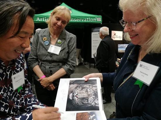 张东光为参加展览的艺术家签名