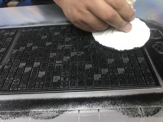 上海字模一厂副厂长刘现云演示拓印铅活字排版的《兰亭序》。